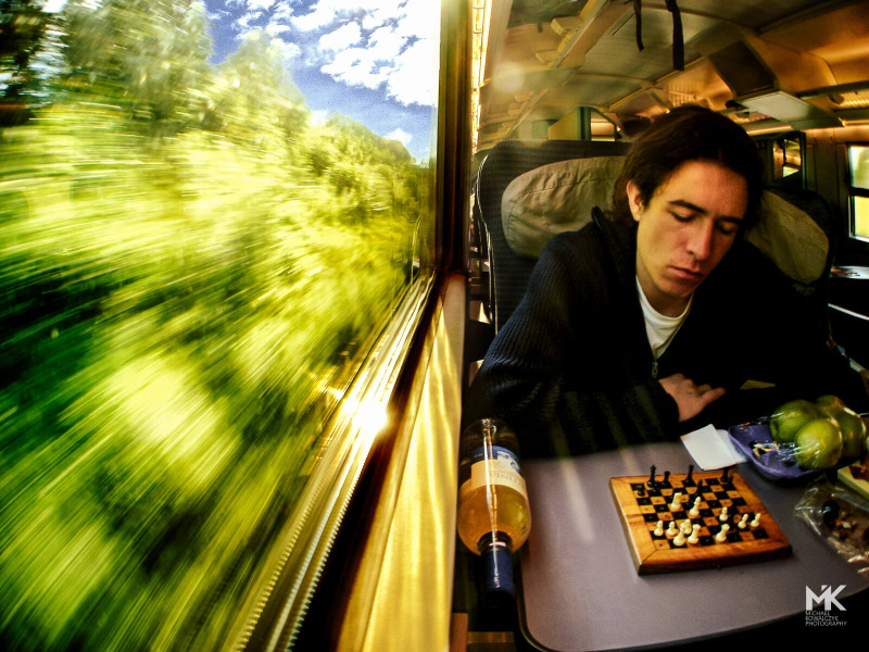 Sitting by the train window and looking at a chess game while traveling trough green woods.