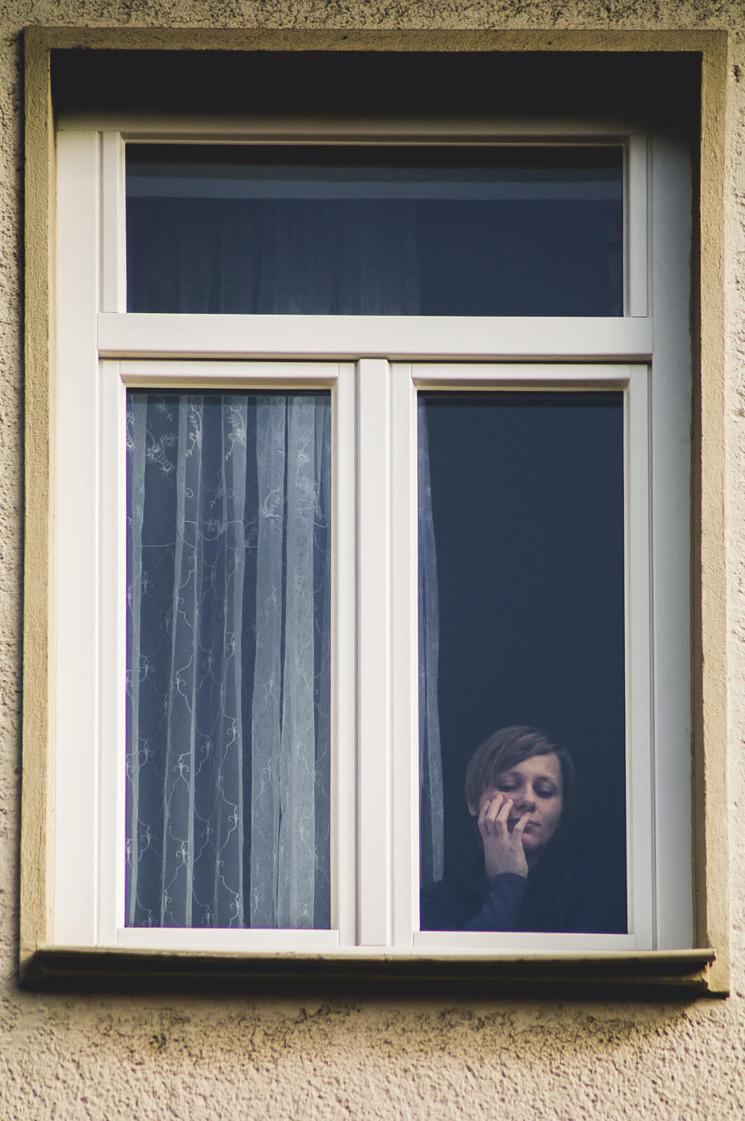 A young woman is looking down on the street behind closed wiindows