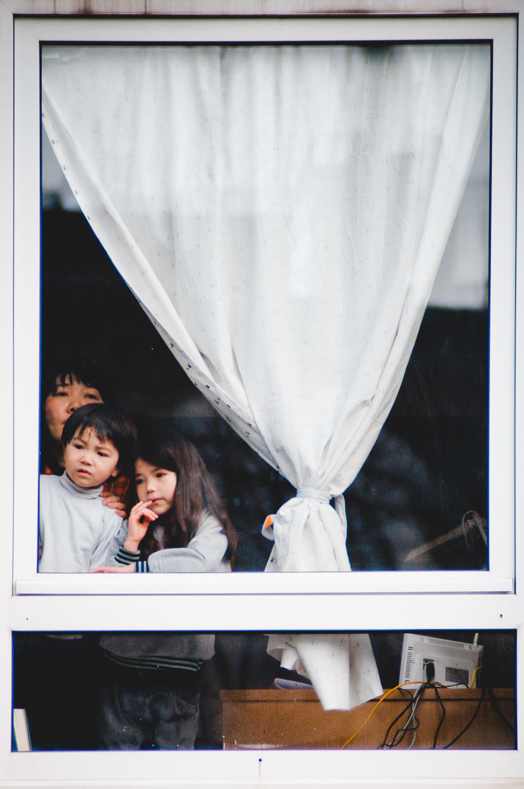Two asian kids and their mother stading behind a closed window and wondering what is going on outside