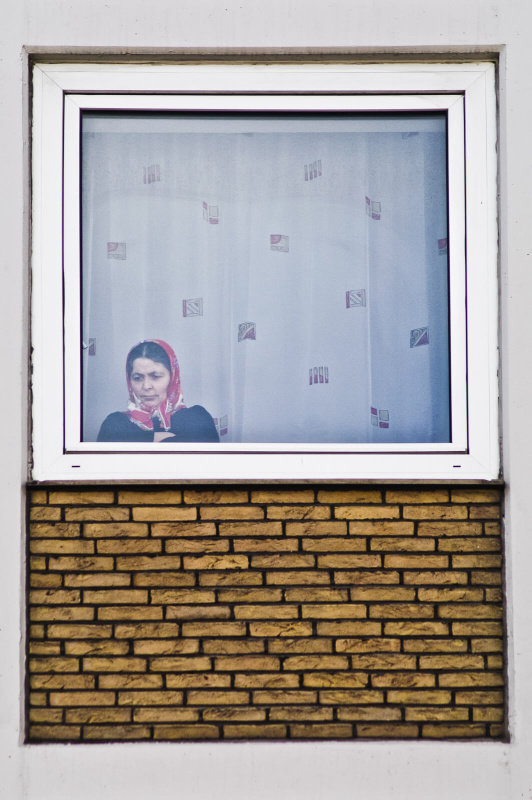 window frame portrait, yellow brick wall, red head scarf