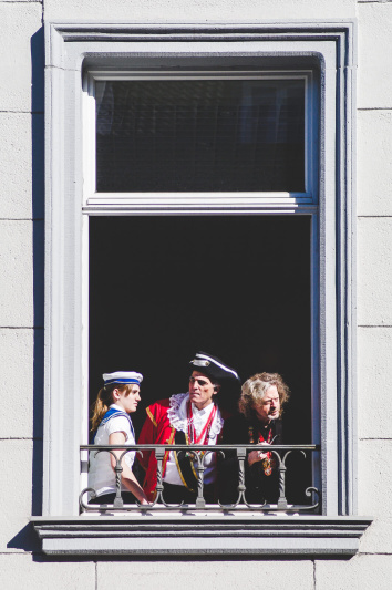 Three men dressed as ancient sailorman standing inside an open window and looking on the street