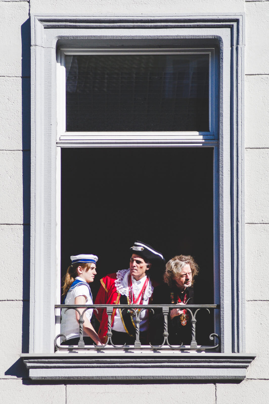 window frame portrait, carnival parade spectator, sailor costume, white brick wall,