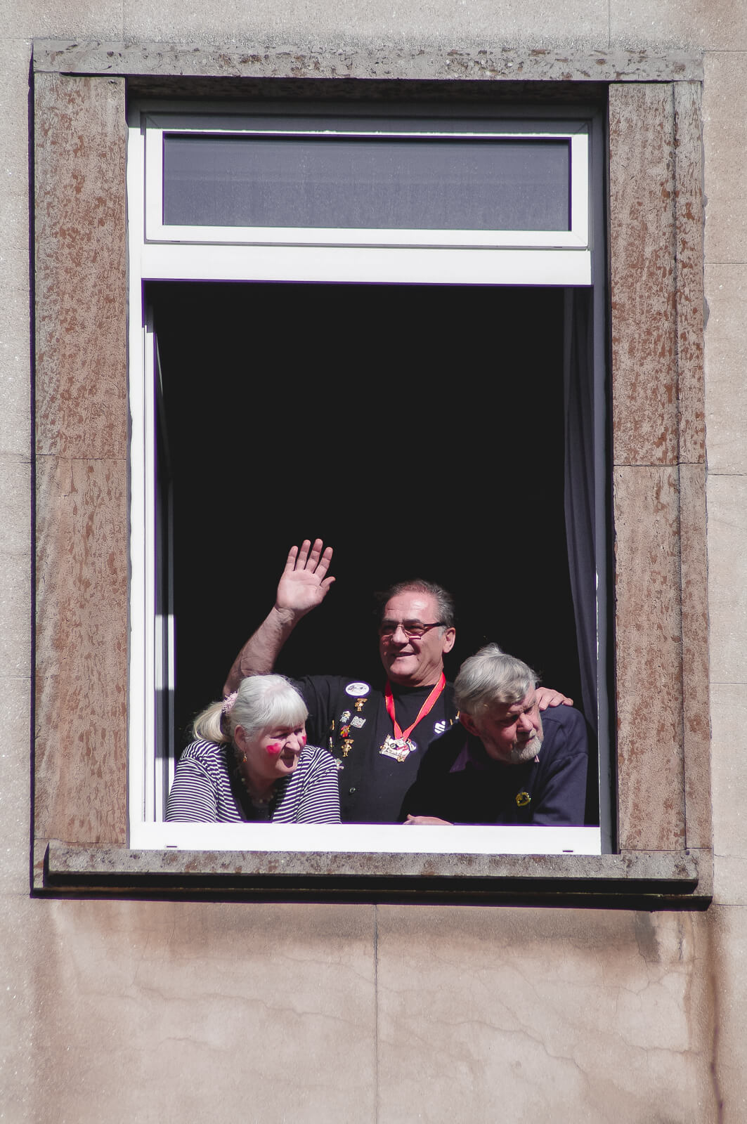 Three middle aged people looking and greeting people out of their open window