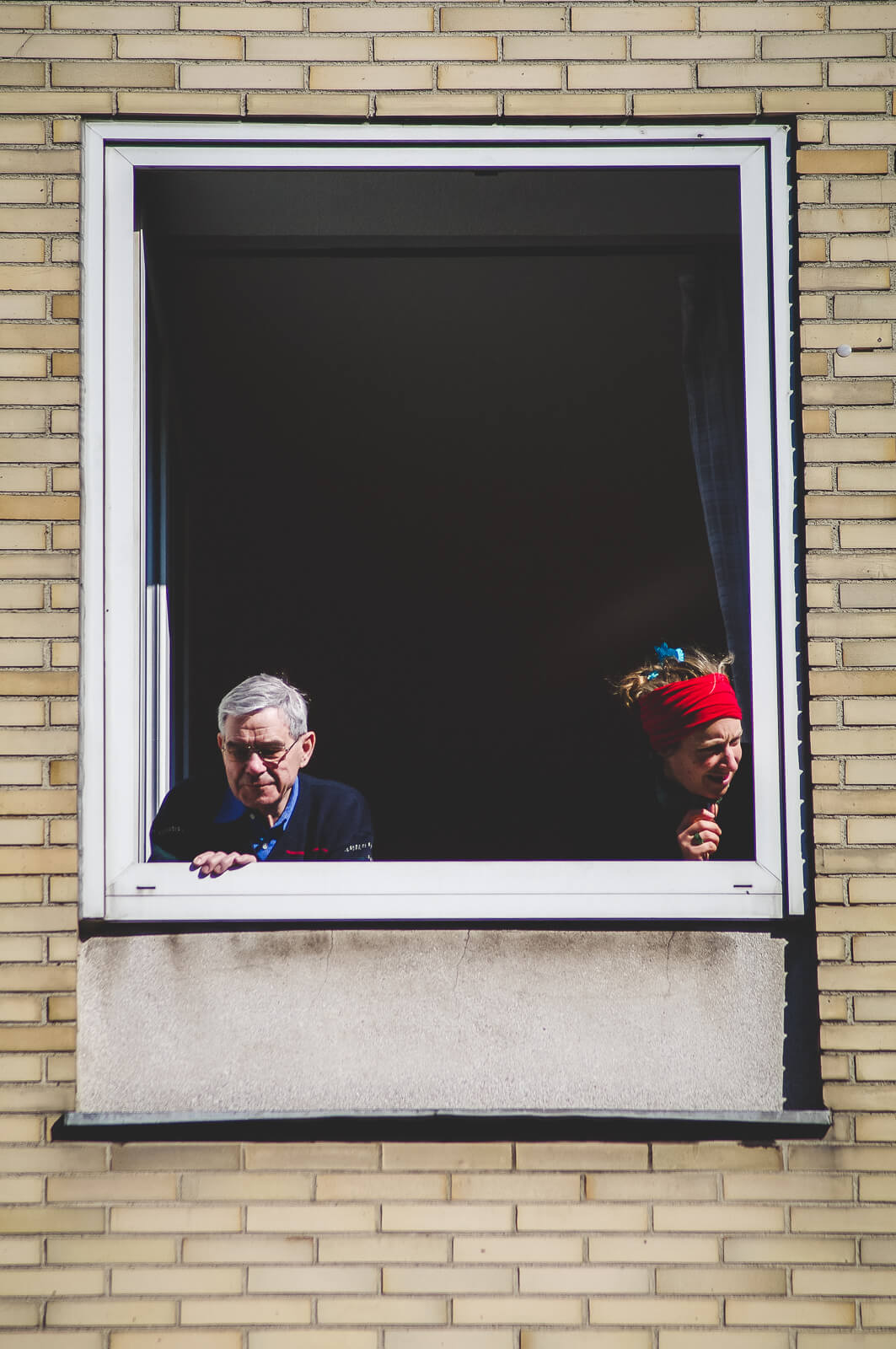 Two people leaning out of the window each on another side