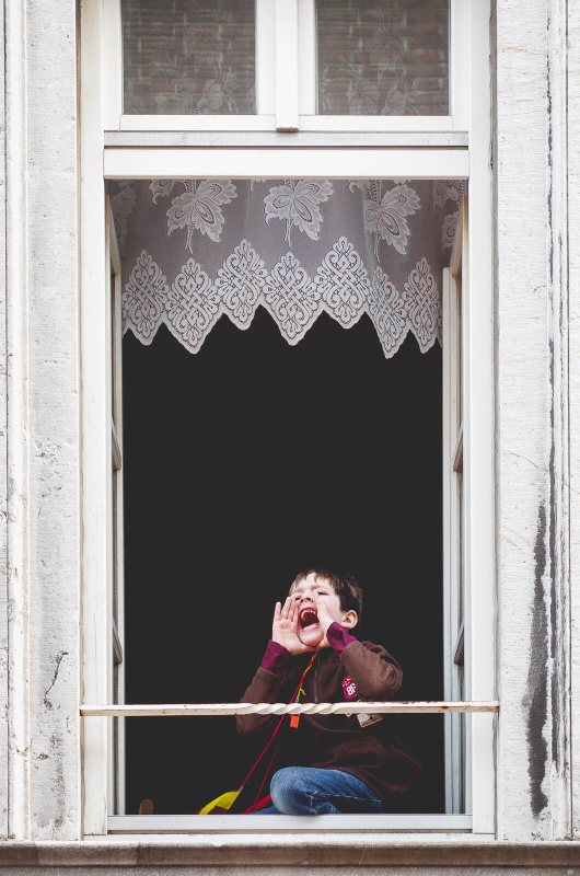 window frame portrait, boy shouting, fang teeth curtain, carnival parade spectator