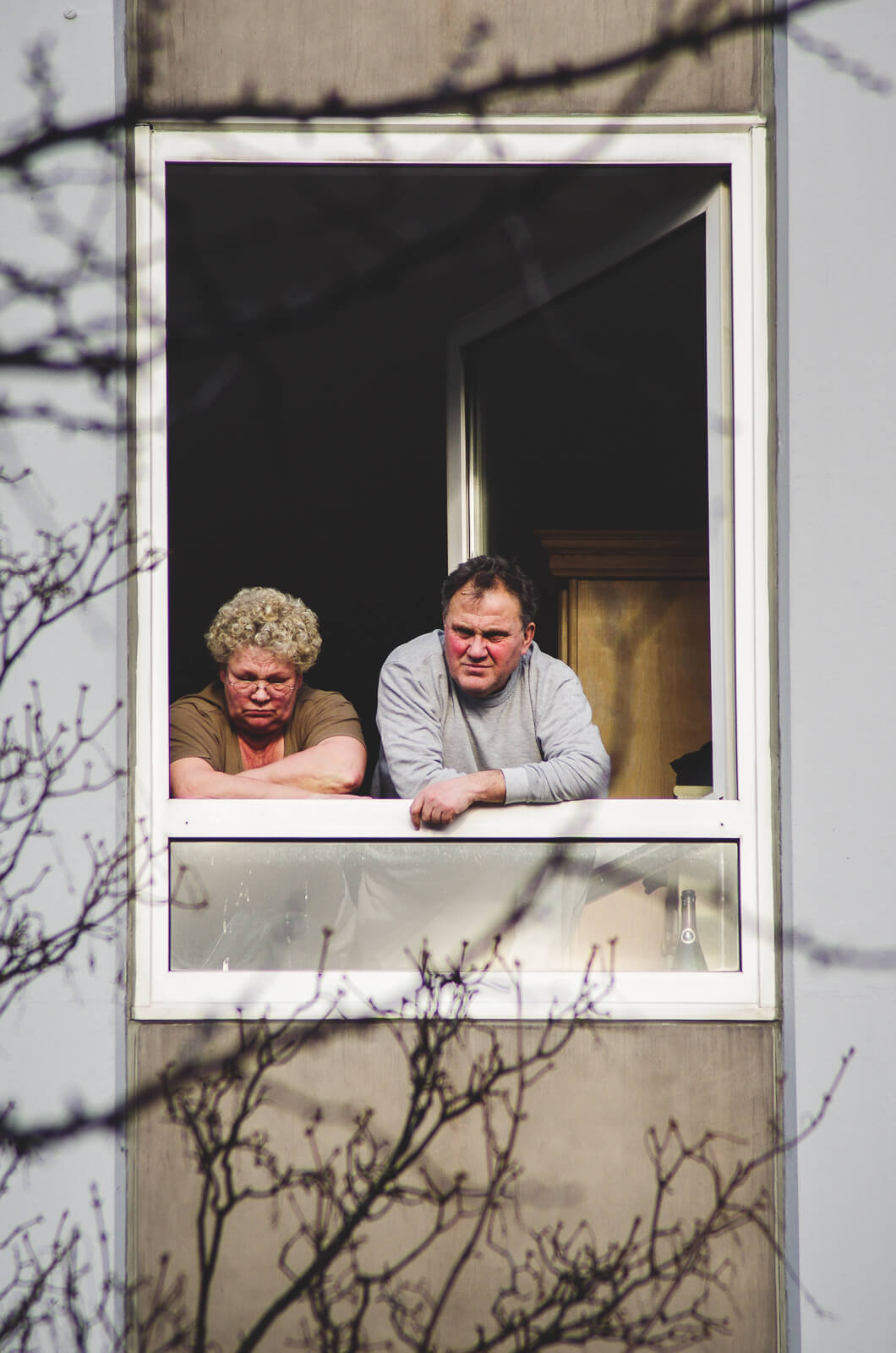 Middle aged German couple leaning out out a open window and looking down on the street