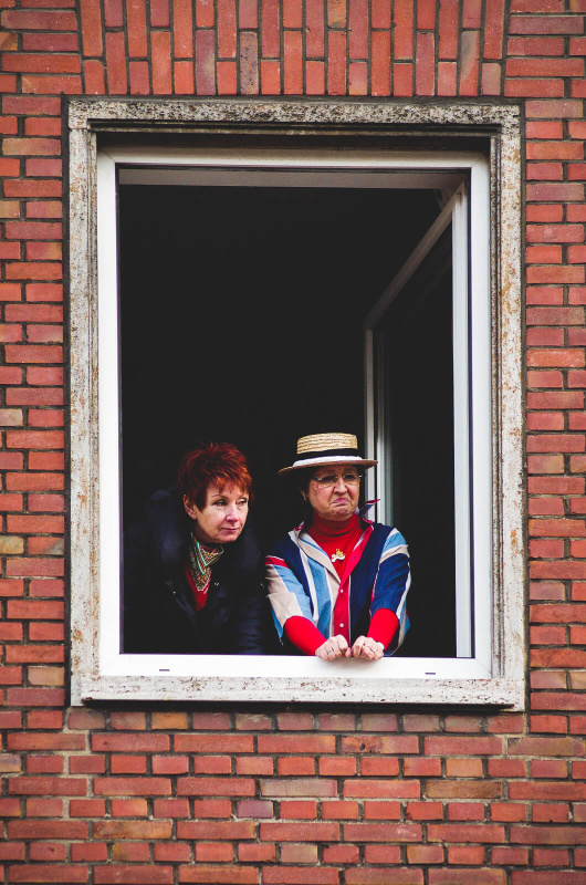 window frame portrait, , carnival parade spectator, skeptic look hat, red brick wall