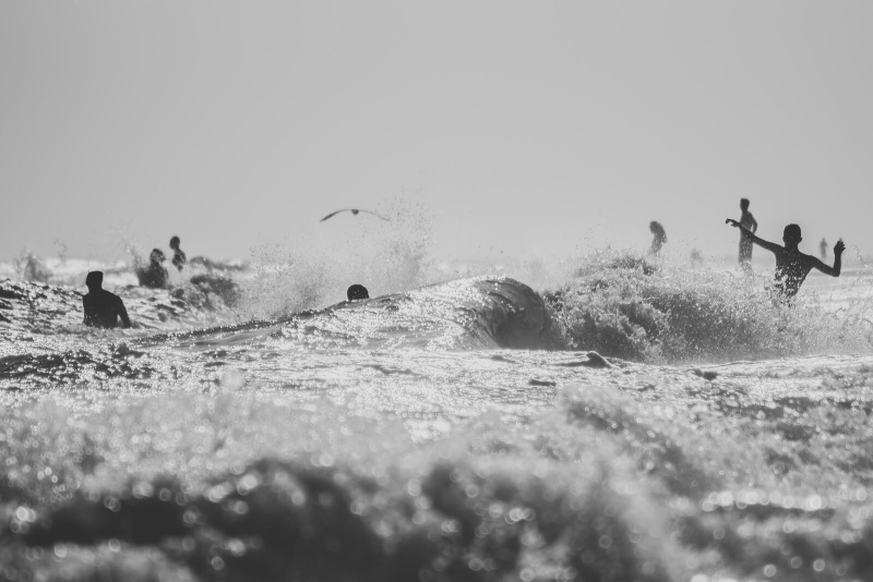 black and white, flying arms silhouette, ocean waves crushing
