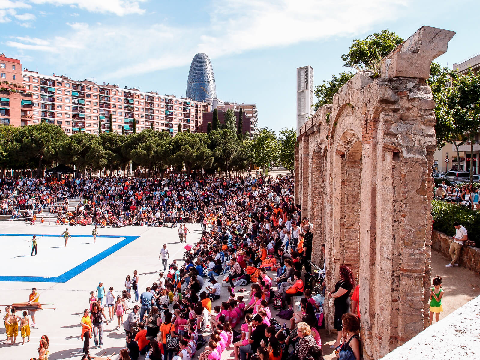Barcelona Street Photography, Parc del Clot buildings, antique arches ruins, children sport event spectators, torre agbar