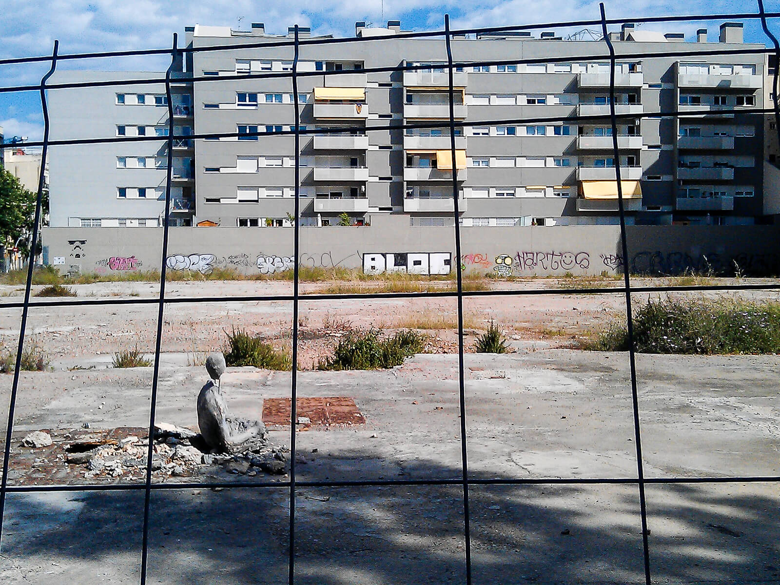 Barcelona Street Photography, building fence, gray beton, stone figure, street art sculpture