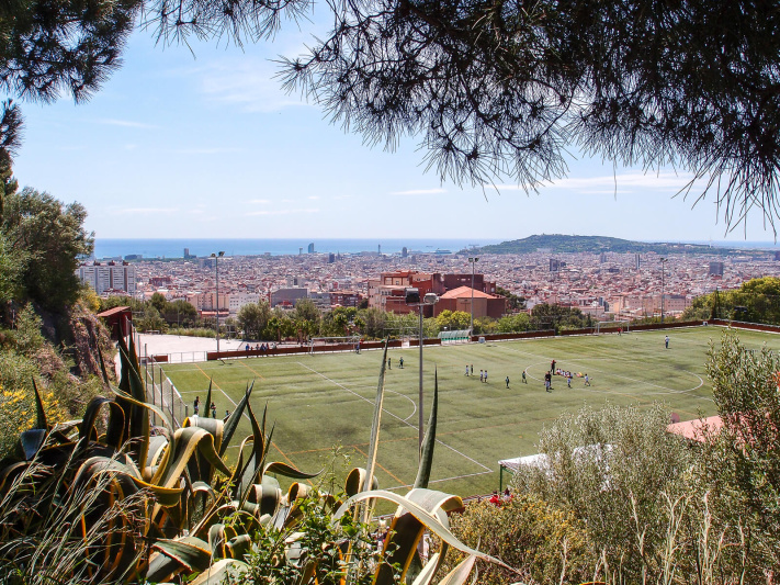 Barcelona city panorama, green football fileld, park Montjuic, passeig auigues