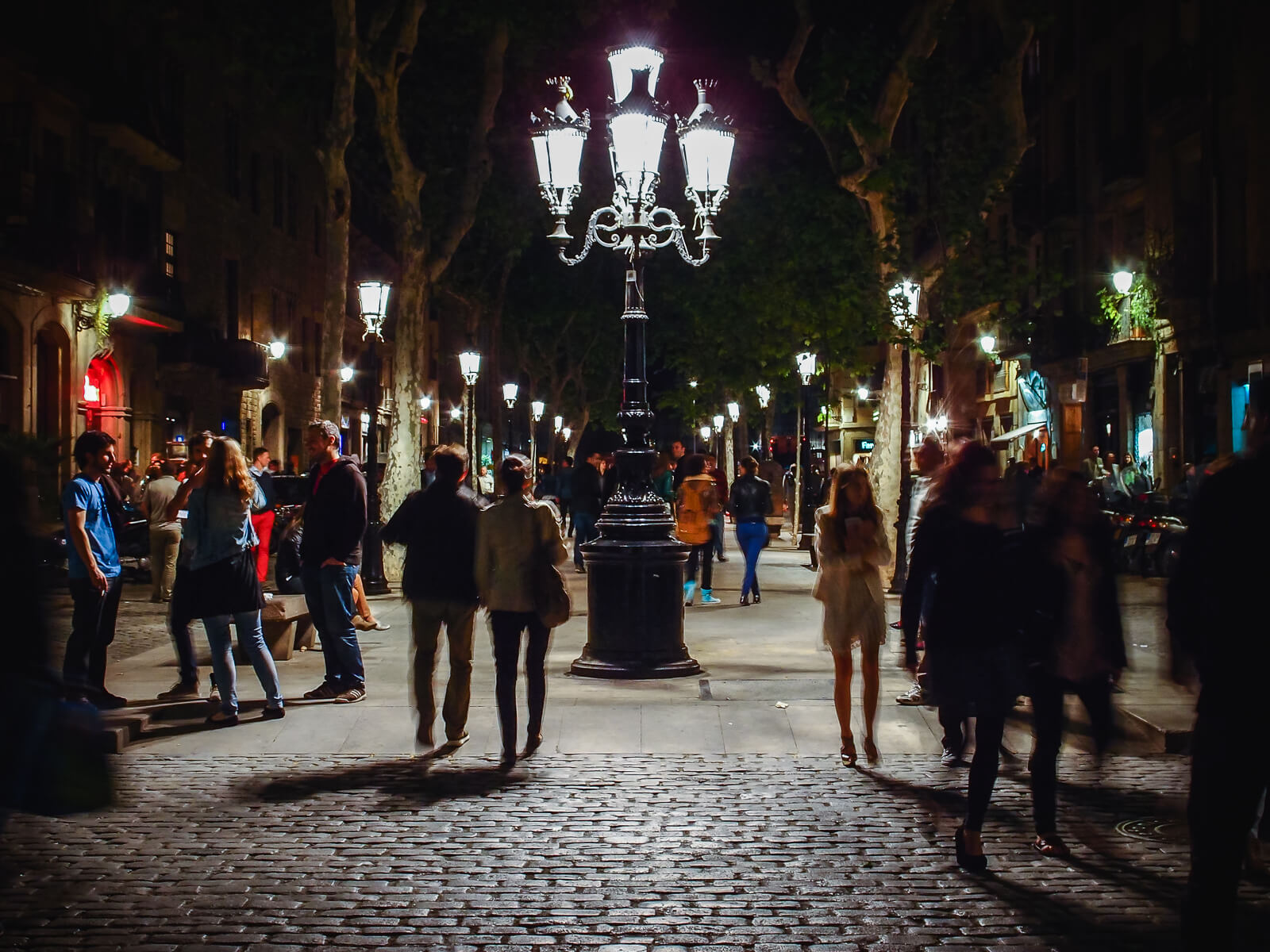 Barcelona Street Photography, curlicue street lamp, narrow tree alley, pedestriants passing, romantic night walk