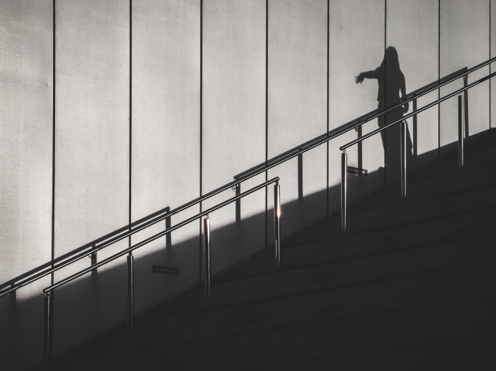 Barcelona, fingers pointing, outdoor stairs, shiny handrail, silver gray background, theatrical act, woman silhouette