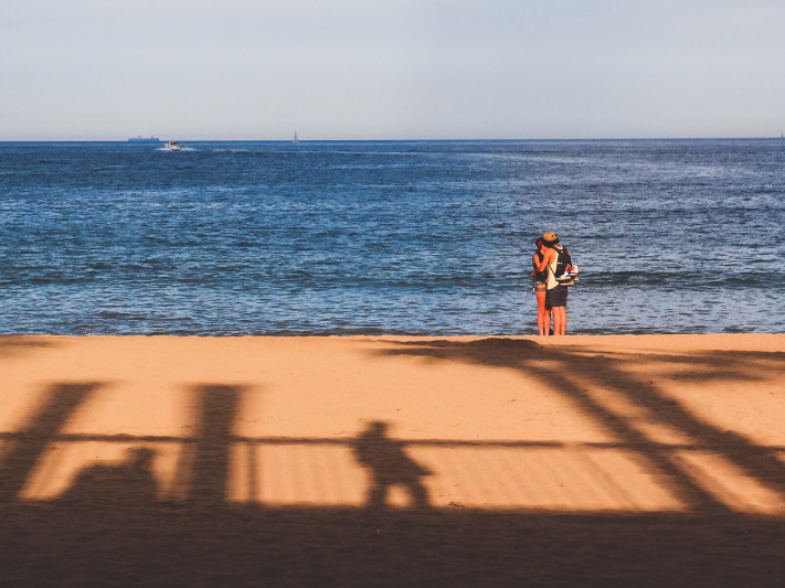 Barcelona beach kiss, palm tree, sunset silhouette, young couple