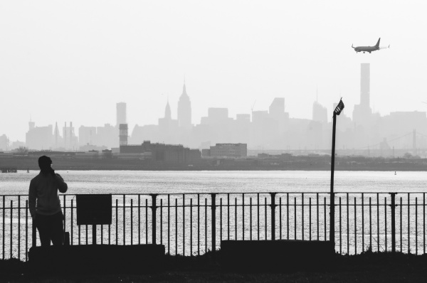 A man watches an Airplane flying over the distant Skyline of Manhattan to land on the LaGuardia Airport.