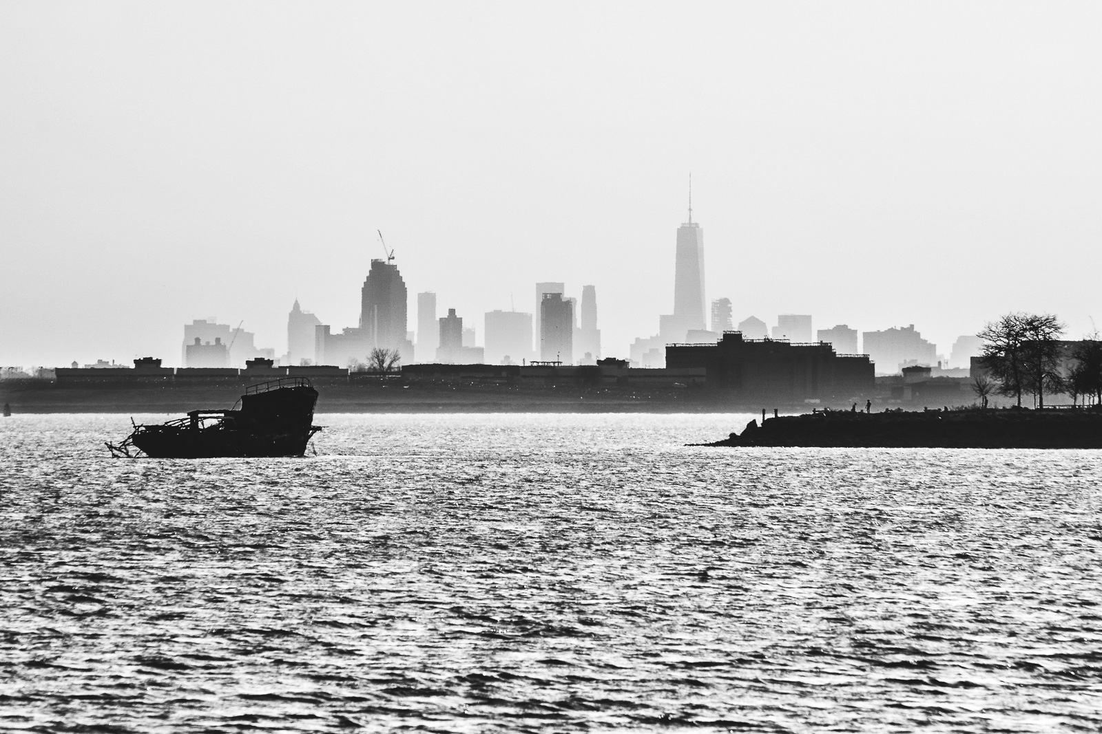 A Ship Wreck is lying in the East River with the distant Skyline of Manhattan in the Background