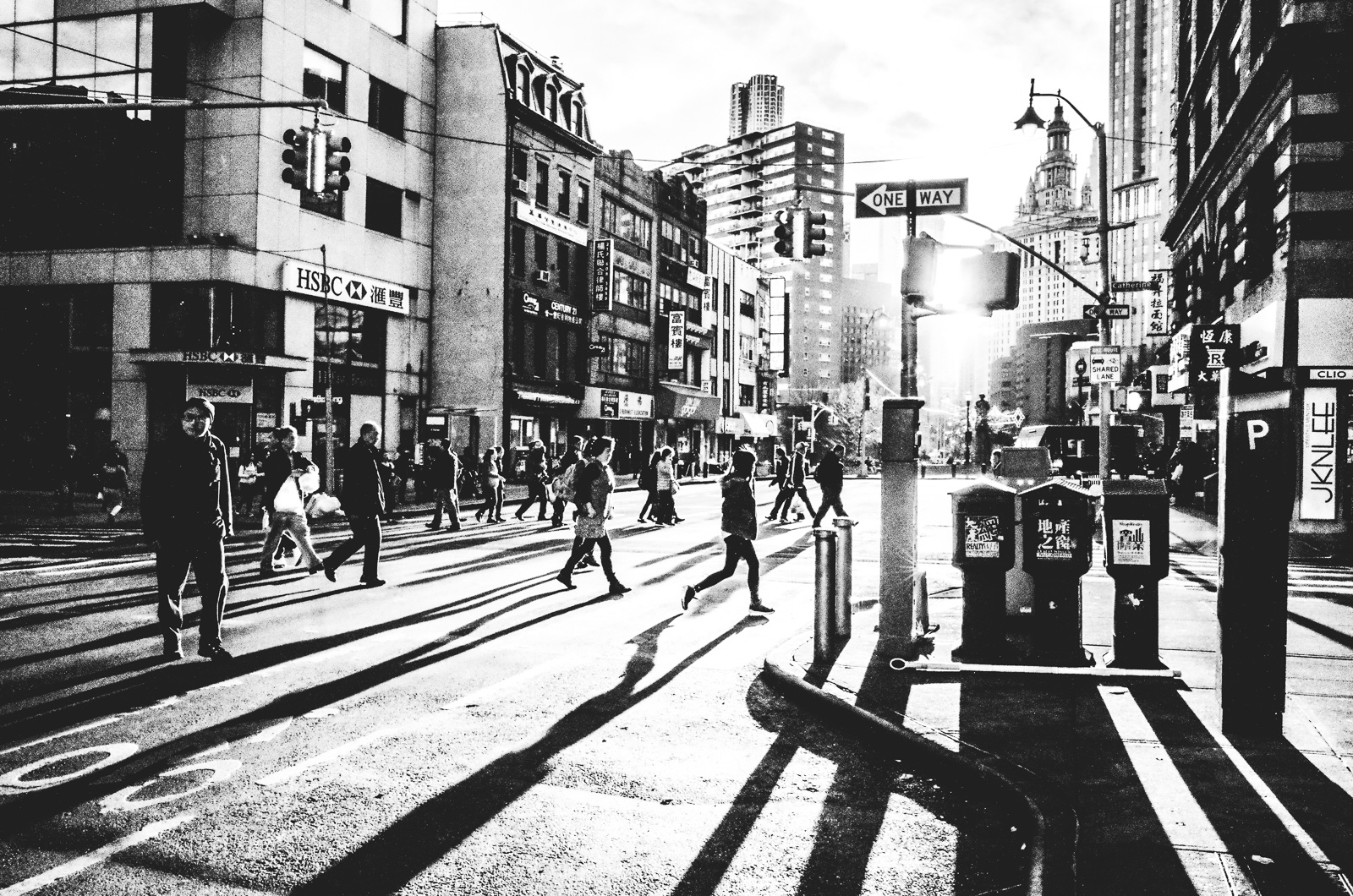 People walk and cast long silhouette shadows on East Broadway Street during Sunset in New York City