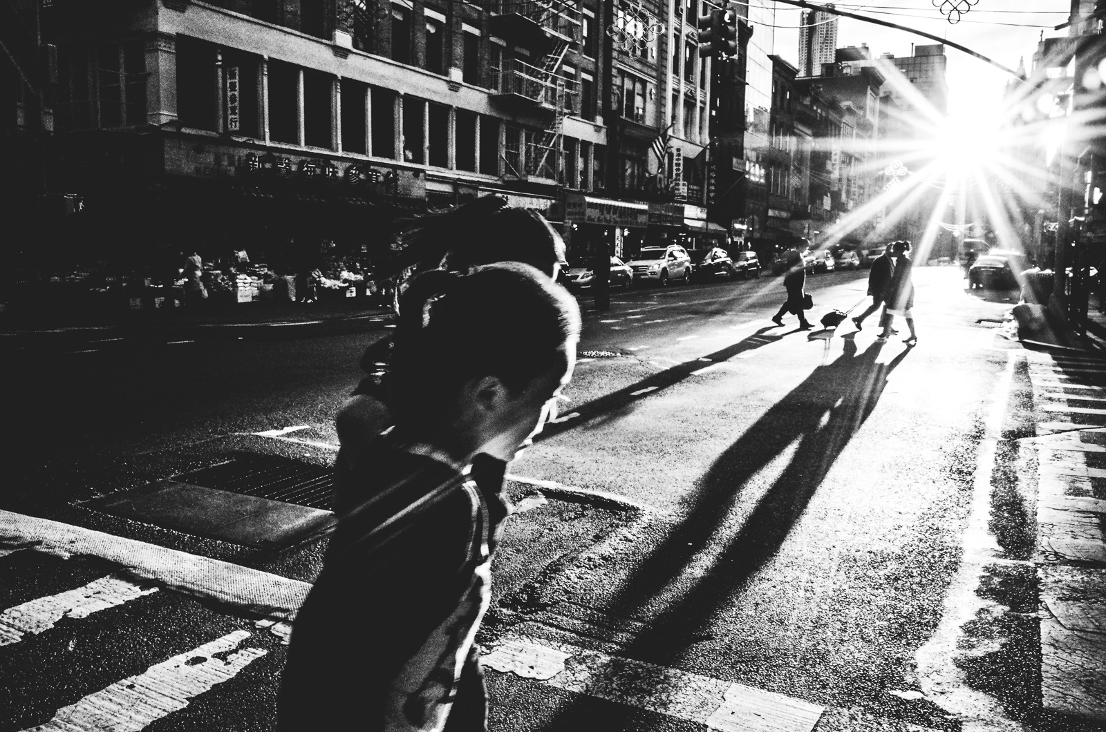 People cast long shadows along East Broadway Street in New York City