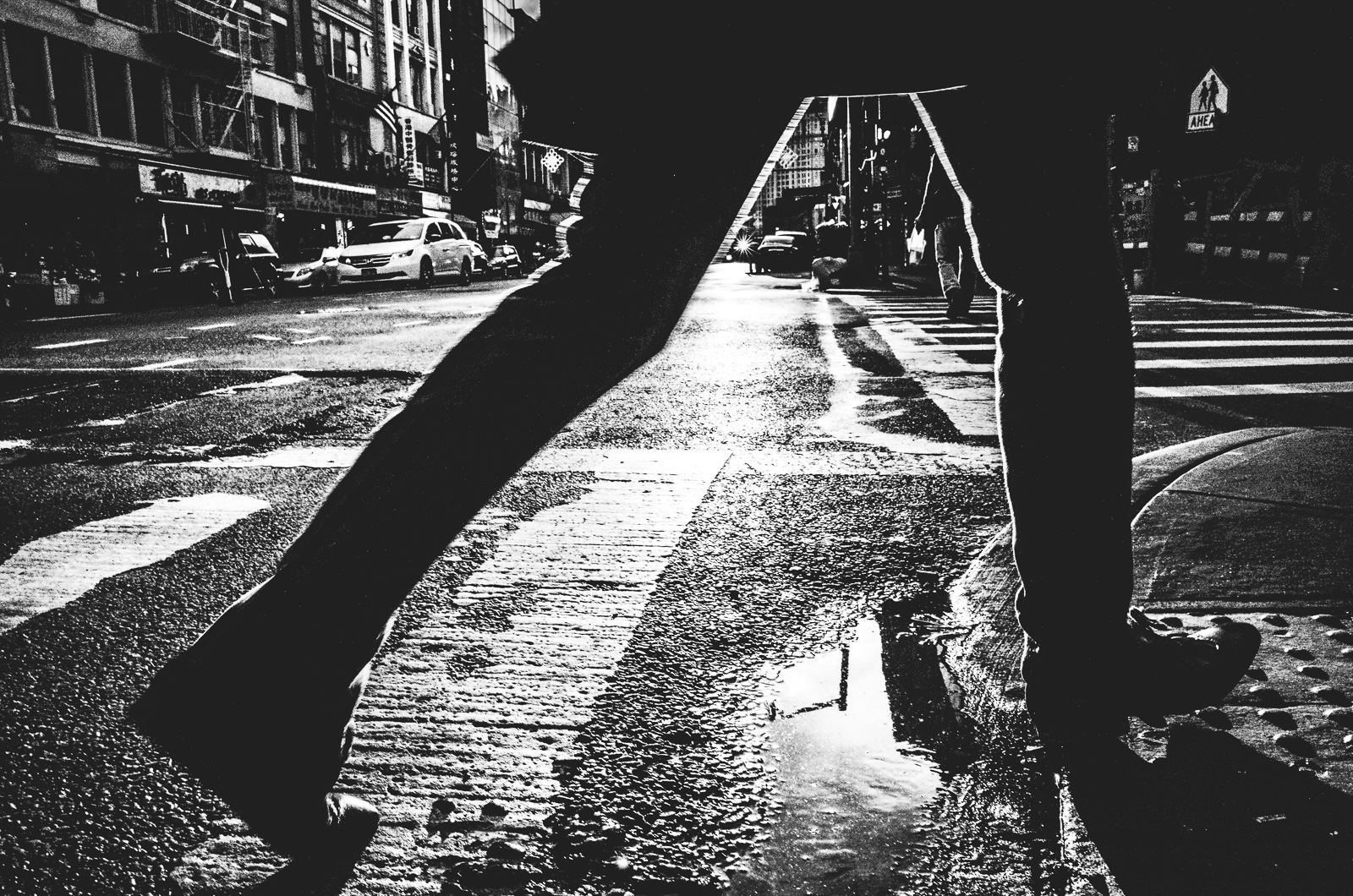 Man steps over a  puddle onto a sidewalk on East Broadway Street in New York City