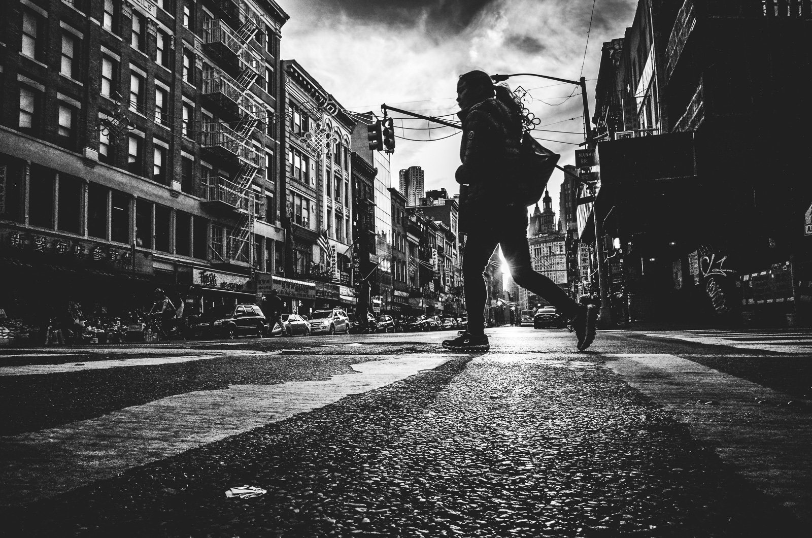 A woman silhouette walks across East Braodway Street in New York City