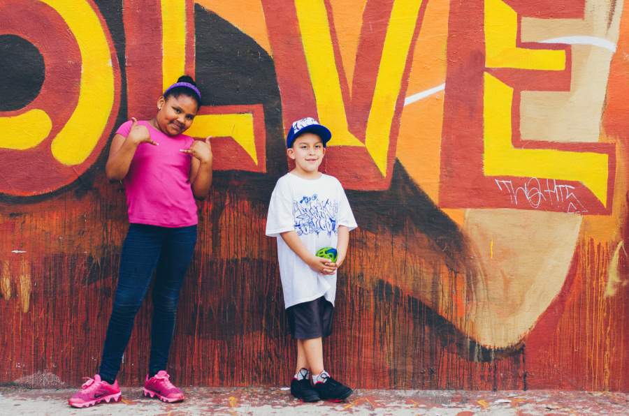 Two kids posing in front of a mural on the Bushwick Collective Block Party 2016