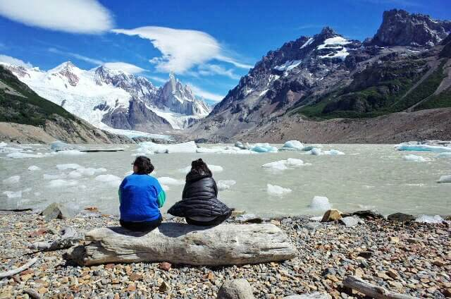 Two sitting on a tree log watching Laguna Torre Fritz Roy